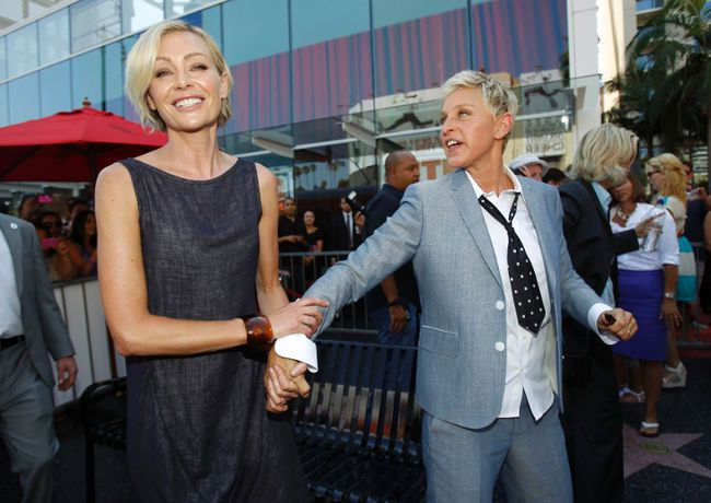 Television personality Ellen DeGeneres holds the hand of her wife actress Portia de Rossi after her star was unveiled on the Walk of Fame in Hollywood, California September 4, 2012. REUTERS/Mario Anzuoni