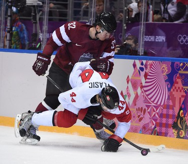 Latvia's Arturs Kulda checks Team Canada's Marc-Edouard Vlasic during men's ice hockey quarterfinals play-off game at the Bolshoy Ice Dome during the Sochi 2014 Winter Olympics in Sochi, Russia, on Wednesday Feb. 19, 2014. Ben Pelosse/Journal de Montreal/QMI Agency OLY2014