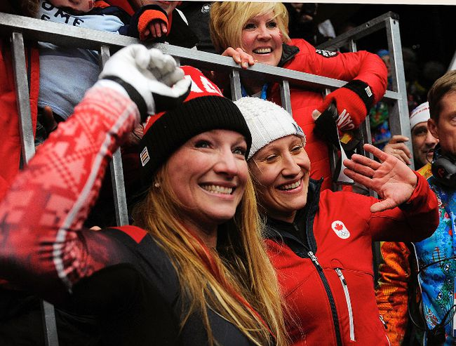 Canada's Kaillie Humphries (right) and Heather Moyse are surrounded by family after their gold medal win in bobsled at the Sanki Sliding Center in Sochi, Russia, Feb. 19, 2014. (DIDIER DEBUSSCHERE/QMI Agency)
