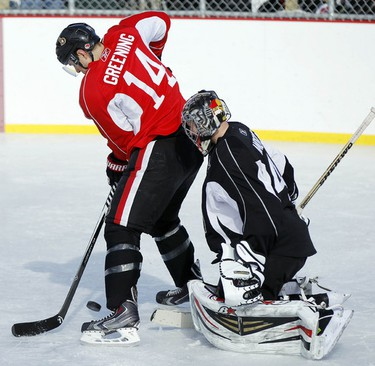 The Ottawa Senators hockey team took to the ice at Jules Morin Park in Ottawa for an outdoor practice on Thursday February 20, 2014. Colin Greening, left, looks to tip a puck in front of Craig Anderson. Darren Brown/Ottawa Sun/QMI Agency