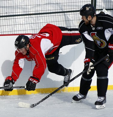 The Ottawa Senators hockey team took to the ice at Jules Morin Park in Ottawa for an outdoor practice on Thursday February 20, 2014. Erik Condra, left, falls after being bumped by Joe Corvo, right. Darren Brown/Ottawa Sun/QMI Agency