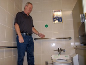 Doug Marks, director of terminal services, explains that with a simple wave of your hand, a new plastic, sanitary toilet seat cover comes out of their new toilet seats installed in the public washrooms at the Grande Prairie Airport in Grande Prairie Alberta on Thursday, Feb. 13, 2014. JOCELYN TURNER/QMI AGENCY