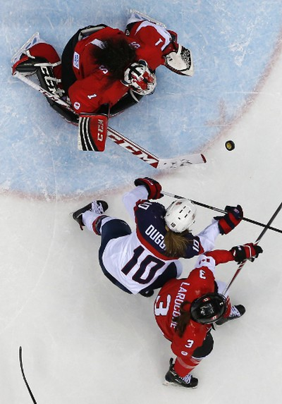 Canada's goalie Shannon Szabados (top) makes a save as Team USA's Meghan Duggan (10) and Canada's Jocelyne Larocque (3) battle for a rebound during the first period of their women's ice hockey gold medal game at the Sochi 2014 Winter Olympic Games February 20, 2014.  REUTERS/Grigory Dukor (RUSSIA  - Tags: SPORT ICE HOCKEY OLYMPICS)