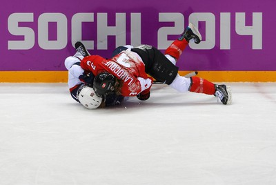 Canada's Jocelyne Larocque (3) and Team USA's Monique Lamoureux fall to the ice during the first period of their women's ice hockey gold medal game at the Sochi 2014 Winter Olympic Games February 20, 2014.  (REUTERS/Laszlo Balogh)