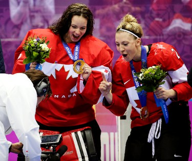 Team Canada players Shannon Szabados of Edmonton, AB. and Meghan Agosta-Marciano of Ruthven, ON., mug for a TV camera as they celebrated beating Team USA 3-2 in overtime to win the women's ice hockey gold medal at the Bolshoy Ice Dome at the Sochi 2014 Winter Olympics in Sochi, Russia, on Thursday Feb. 20, 2014. Al Charest/Calgary Sun/QMI Agency OLY2014