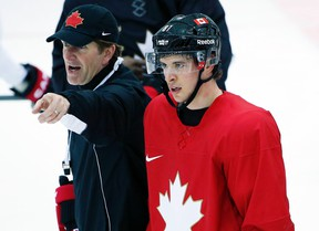 Canadaian men's hockey head coach Mike Babcock gives directions during practice as Sidney Crosby skates by at the 2014 Sochi Winter Olympics, Feb. 18, 2014. (JIM YOUNG/Reuters)