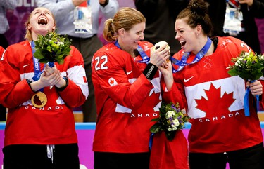 Calgary Sun's photographer Al Charest, in Sochi for the Olympics, snapped a winning photo of Canada gold after the women's hockey team came from behind to beat the U.S. 3-2 in overtime on Thursday, in a game for the ages. Here, Haley Irwin, Hayley Wickenheiser and Natalie Spooner celebrate their victory.