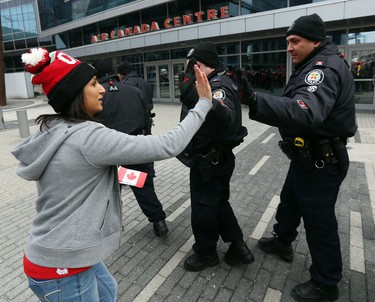 A woman high fives the Toronto police at the end of the game.  Toronto fans gathered at Maple Leaf Square beside the Air Canada Centre to watch the Team Canada men's hockey team win the gold medal against Sweden on Sunday February 23, 2014. Michael Peake/Toronto Sun/QMI Agency