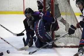 Strathroy Rockets goalie Tynan Lauziere eyes a rolling puck while Chatham Maroons forward and Watford native Kyle Brothers reaches for the disk during GOJHL play Saturday at the West Middlesex Memorial Centre. The Rockets – who won the game 5-4 in overtime – will take on Brothers and the Maroons in Round 1 of the post season. JACOB ROBINSON/AGE DISPATCH/QMI AGENCY