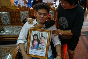 Thayakorn Yosubon, the father of a pair of siblings killed in Sunday's bomb blast near an anti-government protest site, mourns as he hold a photograph of his children during their funeral at a Buddhist temple in Bangkok February 24, 2014.   REUTERS/Athit Perawongmetha