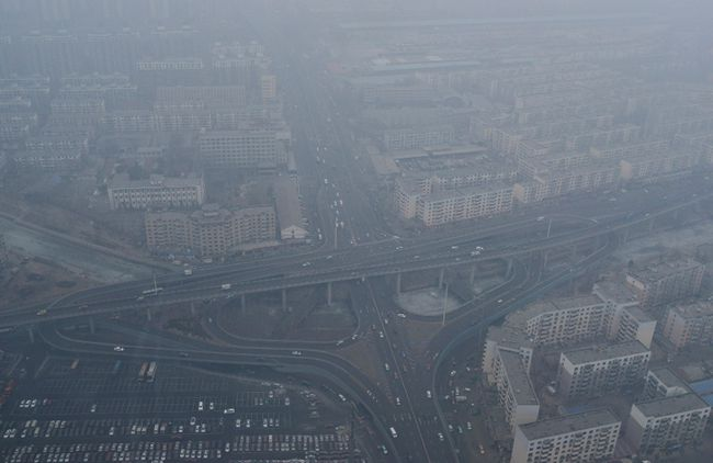 Vehicles travel on a viaduct next to residential buildings amid thick haze in Shenyang, Liaoning province February 24, 2014.  REUTERS/Stringer