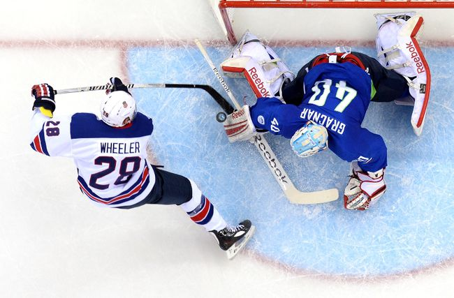 Blake Wheeler vies with Slovenia's goalkeeper Luka Gracnar Feb. 16, 2014. (AFP PHOTO/JONATHAN NACKSTRAND)