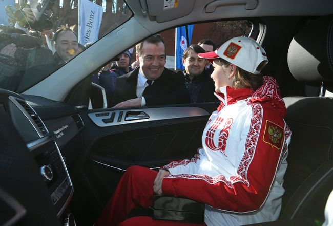 Russian Prime Minister Dmitry Medvedev and figure skating gold medal winner Yulia Lipnitskaya (front) attend a ceremony to present SUVs to the Olympic medallists from Russia near the Kremlin wall in Moscow, February 27, 2014.  (REUTERS/Ekaterina Shtukina/RIA Novosti/Pool)