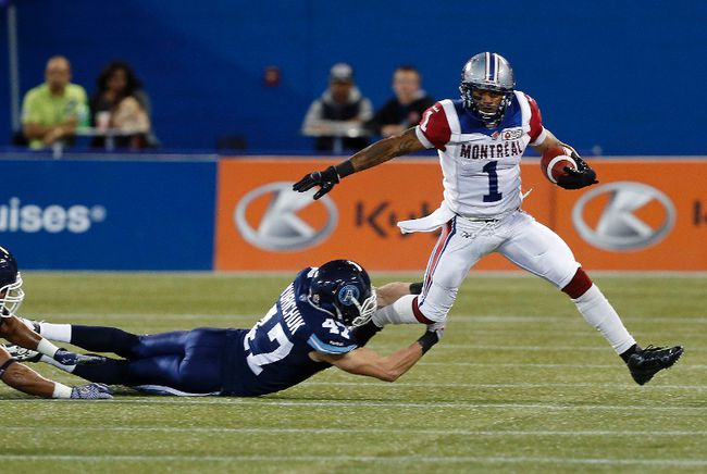 James Yurichuck of the Toronto Argonauts tackles Arland Bruce of the Montreal Alouettes during CFL action in Toronto Friday, November 1, 2013. (STAN BEHAL/QMI Agency)