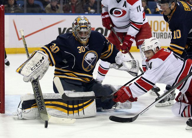 Buffalo Sabres goalie Ryan Miller makes a stick save as Carolina Hurricanes winger Nathan Gerbe (14) dives for the rebound during the first period at First Niagara Center Feb. 25, 2014. (Timothy T. Ludwig/USA TODAY Sports)