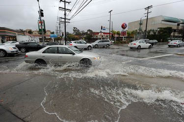 A car drives through a flooded intersection in Studio City, California, six miles (nine km) north of Hollywood, California, February 28, 2014.  Heavy rains hit southern California overnight and though much needed in the drought-stricken region, the heavy downpour risks causing mudslides and flooding.  The National Weather Service predicts more heavy rains leading up to Oscar Sunday.  AFP PHOTO / ROBYN BECK