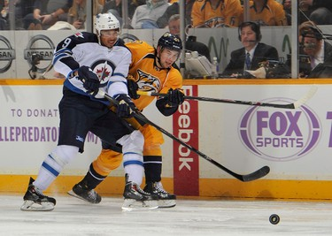 NASHVILLE, TN - MARCH 01: Simon Moser #21 of the Nashville Predators skates against Evander Kane #9 of the Winnipeg Jets at Bridgestone Arena on March 1, 2014 in Nashville, Tennessee.   Frederick Breedon/Getty Images/AFP == FOR NEWSPAPERS, INTERNET, TELCOS & TELEVISION USE ONLY ==