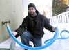Ryan Black has had to use a hose to get water from a neighbour's house in Winnipeg, Man. Wednesday February 26, 2014. Black has been without water for a month due to frozen pipes. The city is now offering city pool facilities for those who want to take showers, as well as more hoses like this. (Brian Donogh/Winnipeg Sun/QMI Agency)
