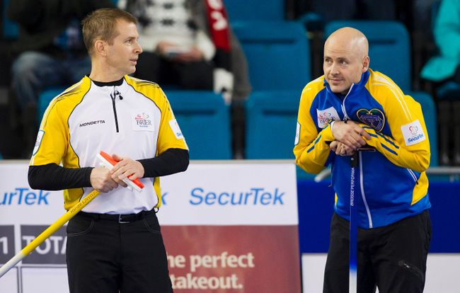 Team Manitoba skip Jeff Stoughton (left) talks to Team Alberta skip Kevin Koe before their draw during the 2014 Brier curling championship in Kamloops, B.C., March 3, 2014. (BEN NELMS/Reuters)