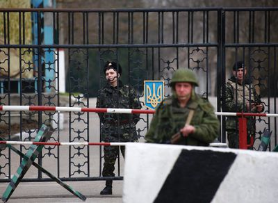 An armed man, believed to be a Russian serviceman, stands outside a Ukrainian military post as Ukrainian servicemen look on from behind a gate in the Crimean city of Kerch March 4, 2014. Russia has agreed to a meeting with representatives from NATO on Wednesday to discuss the Ukraine crisis, Italian Foreign Minister Federica Mogherini said on Tuesday. REUTERS/Thomas Peter
