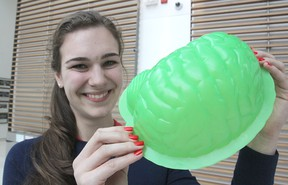 Queen's University psychology student Alex Wolfer shows the mould of a brain that is filled with Jell-O during a special presentation on the organ for elementary school students this month. The event seeks to educate the children on brain injuries and safety. Michael Lea The Whig-Standard