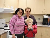 Grey-Bruce Eat and Learn Nutritional Program volunteers Brenda Sorensen (left) and Debbie Price (right) with Hanover Heights Grade 4 student Christopher Crozier enjoying a nice crisp apple.