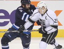 Winnipeg Jets defenceman Mark Stuart (l) ties up Los Angeles Kings right winger Dustin Brown during NHL hockey in Winnipeg, Man. Thursday, March 06, 2014. Brian Donogh/Winnipeg Sun/QMI Agency