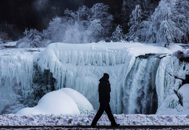 A man walks in front of the partially frozen American side of the Niagara Falls on during sub-freezing  temperatures in Niagara Falls, Ontario March 3, 2014. REUTERS/Mark Blinch