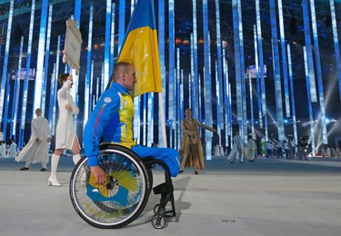 Ukraine's flag-bearer Mykhaylo Tkachenko arrives in the stadium during the opening ceremony of the 2014 Paralympic Winter Games in Sochi, March 7, 2014. (REUTERS)