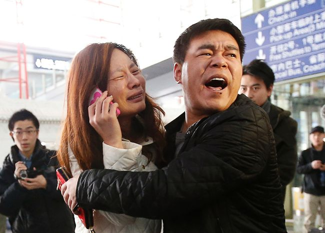 A relative (woman in white) of a passenger onboard Malaysia Airlines flight MH370 cries as she talks on her mobile phone at the Beijing Capital International Airport March 8, 2014.(REUTERS/Kim Kyung-Hoon)