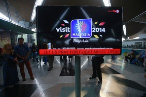 """An information screen displays a message """"Let Us Pray For Flight MH370"""", regarding the missing Malaysia Airlines flight, at Kuala Lumpur International Airport in Sepang, March 8, 2014. REUTERS/Samsul Said"""