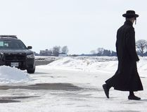 A member of the ultra-orthodox Lev Tahor sect walks across the roadway leading into their enclave at Spurgeon's Villa, north of Chatham, Ont., while Chatham-Kent police keep watch over the community on Wednesday, March 5, 2014. (VICKI GOUGH/ QMI AGENCY)