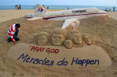 Indian sand artist Sudarshan Patnaik applies the final touches to a sand art sculpture he created wishing for the well being of the passengers of Malaysian Airlines flight MH370, on a beach in Puri, in the eastern Indian state of Odisha, March 9, 2014. (REUTERS/Stringer)
