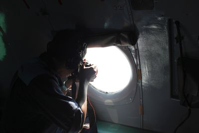 A Vietnamese Air Force officer takes photos from a search and rescue aircraft in the search area for a missing Malaysia Airlines plane, 250 km from Vietnam and 190 km from Malaysia, in this handout photo from Thanh Nien Newpaper taken March 8, 2014. (REUTERS/Trung Hieu/Thanh Nien Newspaper)
