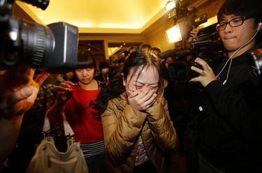 A relative (front) of a passenger of Malaysia Airlines flight MH370 cries as she walks past journalists at a hotel in Beijing March 9, 2014. (REUTERS/Jason Lee)