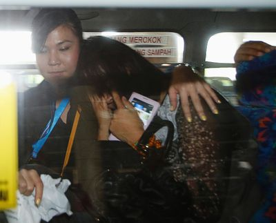 A Chinese relative of a passenger of Malaysia Airlines MH370 is comforted by a staff member of the airport as she shields her face from journalists at Kuala Lumpur International Airport in Sepang March 10, 2014. (REUTERS/Edgar Su)