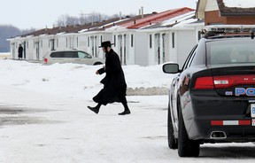 A member of the ultra-orthodox Lev Tahor sect walks across the roadway leading into their enclave at Spurgeon's Villa, north of Chatham, Ont., while Chatham-Kent police keep watch over the community on Wednesday, March 5, 2014. (VICKI GOUGH/QMI Agency)