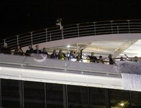 Passengers wait to leave the Carnival Triumph cruise ship after reaching the port of Mobile, Alabama, February 14, 2013. (REUTERS/ Lyle Ratliff)
