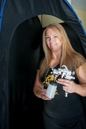 Heather Smith is picture holding the gun she uses to apply tan. While the tan feels very dry soon after application, it cannot get wet for 8-10 hours.