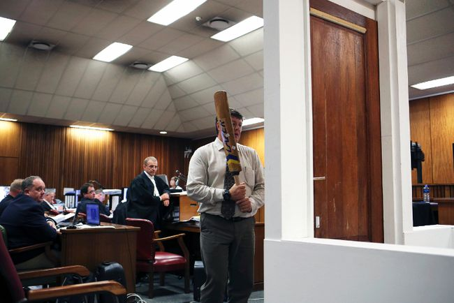 A policeman demonstrates the effect of hitting of a bathroom door with a cricket bat during the trial of South African athlete Oscar Pistorius in the North Gauteng High Court in Pretoria, March 12, 2014.  (ALEXANDER JOE/Reuters/Pool)