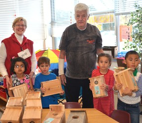 University Heights Public School kindergarten teacher Lynn Hill and some of her students stand around a handful of birdhouses created by James Symons, also pictured. The students have an outdoor class where they learn about nature and they were surprised to receive a birdhouse that they could take home and report their observations back to their classmates.