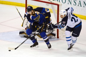 Winnipeg Jets center Patrice Cormier (28) attempts to steal the puck from St. Louis Blues defenseman Alex Pietrangelo (27) during the third period at Scottrade Center. The St. Louis Blues defeat the Winnipeg Jets 4-1.Jasen Vinlove-USA TODAY Sports