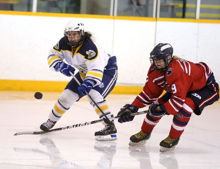 Kaylie Venedam of the College Notre Dame Alouettes and Jillian Banks of the Bear Creek Secondary School Kodiaks fight for the loose puck during OFSAA AAA/AAAA action from the McClelland Arena on Wednesday afternoon.