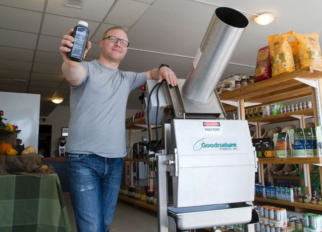 Christian Vemb, co-owner of London's Pulp and Press Juice, shows off the cold press he uses to make trendy fruit and vegetable juices. (DEREK RUTTAN, The London Free Press)