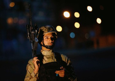 An Afghan security personnel keeps watch near the Serena hotel, during an attack in Kabul March 20, 2014. Taliban gunmen attacked the luxury Serena hotel on Thursday in the centre of the Afghan capital Kabul, police said, and four of the assailants were killed in a shootout with Afghan security forces. REUTERS/Ahmad Masood