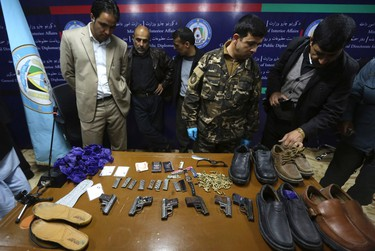 Afghan security officials display the weapons and bullets of Taliban insurgents that were killed last night in a luxury hotel in Kabul March 21, 2014. Taliban gunmen killed nine people, including four foreigners, in an attack on a luxury hotel used by United Nations' staff in Kabul on Thursday, before being shot dead in a shootout with Afghan security forces, police and government officials said. REUTERS/Omar Sobhani