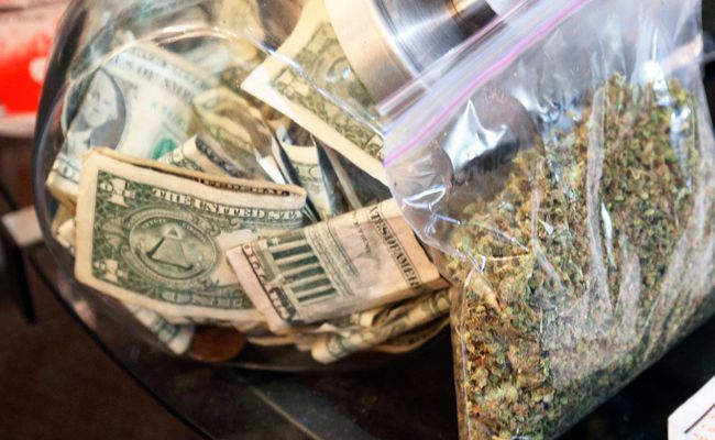 A bag of marijuana being prepared for sale sits next to a money jar at BotanaCare in Northglenn, Colorado in this file photo taken December 31, 2013. (REUTERS/Rick Wilking/Files)