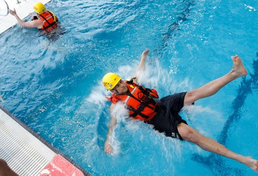 A group of six city firefighters with Station 1 conduct in-pool training prior to train on ice on the Bay of Quinte later this spring, at Quinte Sports and Wellness Centre in Belleville, Ont. Thursday, March 20, 2014. (Jerome Lessard/QMI Agency)