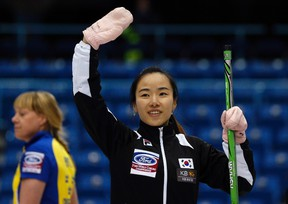 South Korea skip Kim Ji-sun waves to the crowd after defeating Sweden during her tie-breaker game at the world women's curling championship in Saint John, N.B., on Friday, March 21, 2014. (Mathieu Belanger/Reuters)