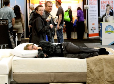A woman tries out a bed at the Sleep Country Canada booth, during the Edmonton Home and Garden Show at the Edmonton Expo Centre, in Edmonton Alta., on Friday March 21, 2014. David Bloom/Edmonton Sun/QMI Agency